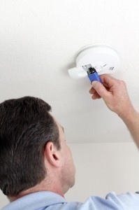 Man changing smoke detectors