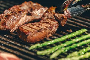 steaks and asparagus cooking on a grill