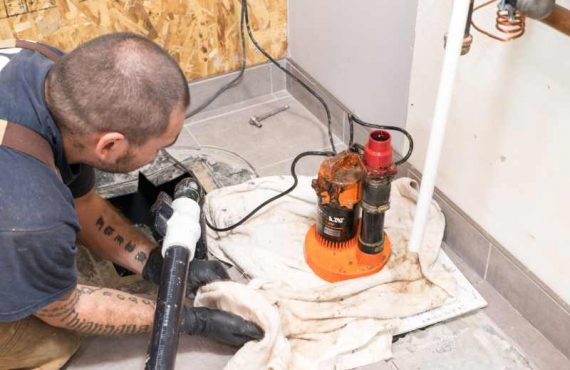 Plumber kneeling on the floor working on a sump pump.