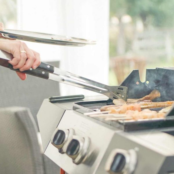 Woman's hand holding tongs above a barbecue.