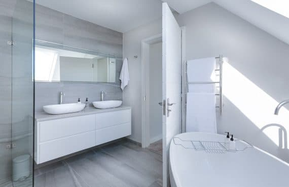 All-white bathroom with a soaker tub and twin sinks.