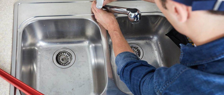 Plumber fixing a kitchen faucet.