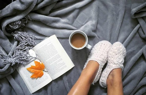 A woman's feet in knit slippers on a bed next to an open book and a cup of coffee.
