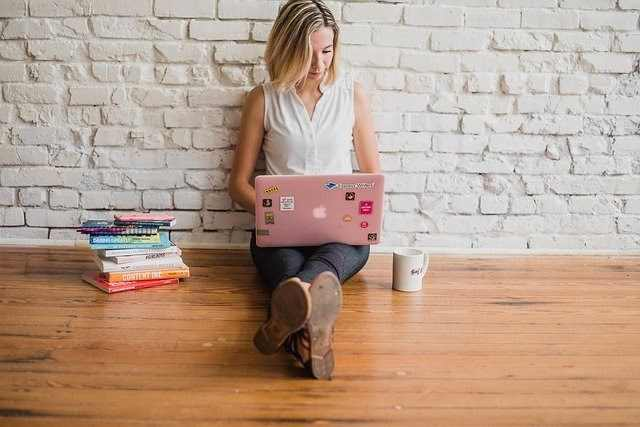 Woman sitting on a wooden floor with a laptop next to a stack of books and a coffee mug.