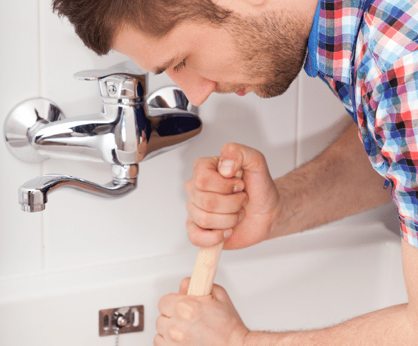 Man in a plaid shirt using a plunger on a bathtub drain.