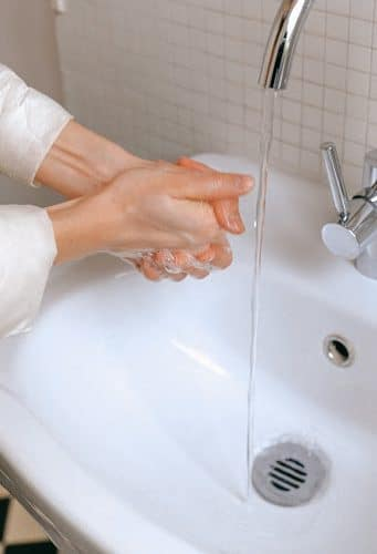 Close up of hands washing in a sink with a weak stream of water.