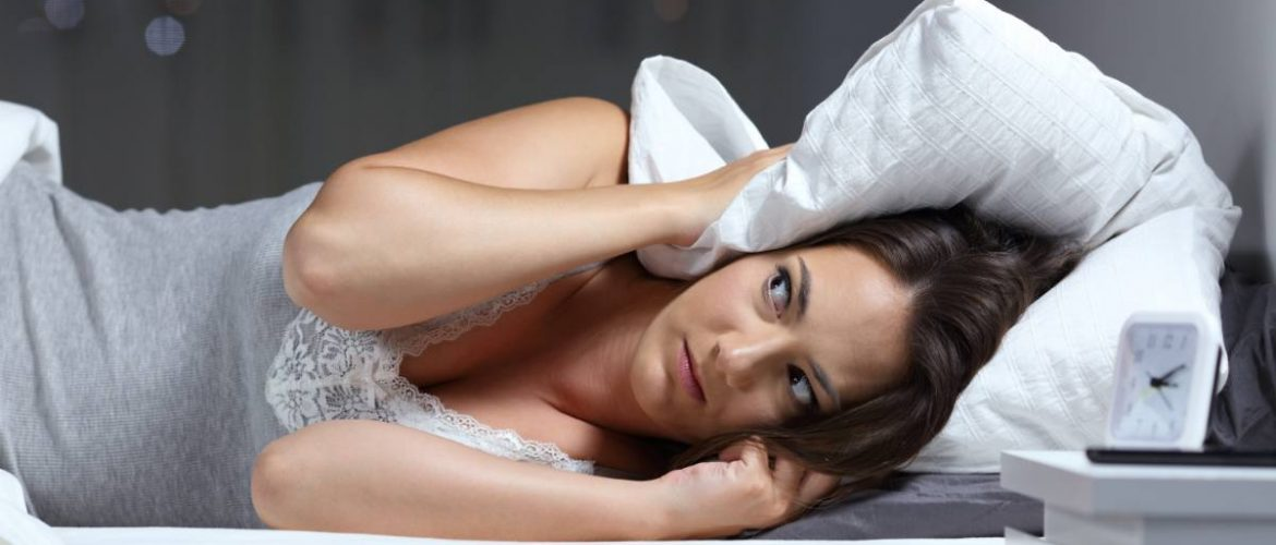 A woman covering her ears with a pillow