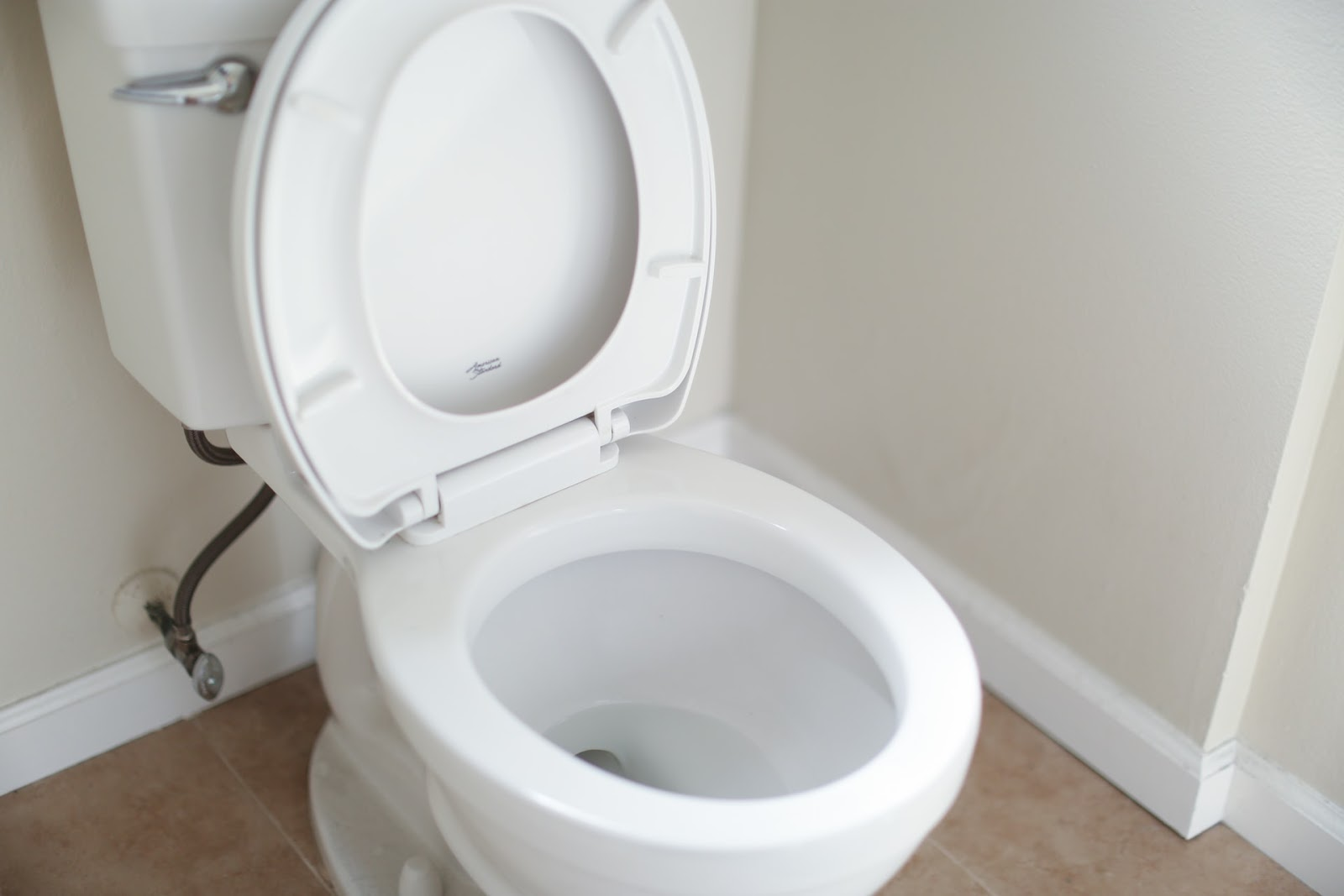 A white toilet with the seat up.