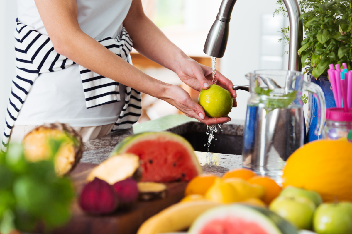 Various fruits on a kitchen counter next to a person washing an apple in the sink.